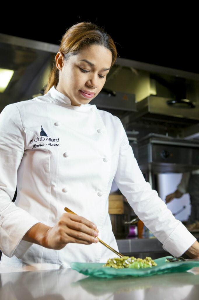 Maria Marte dando los toques finales a uno de sus platos